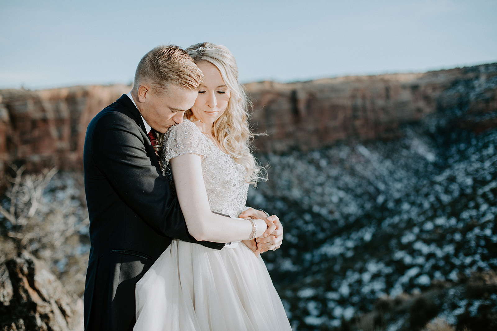 Groom kissing bride's shoulder from behind with red cliff behind them