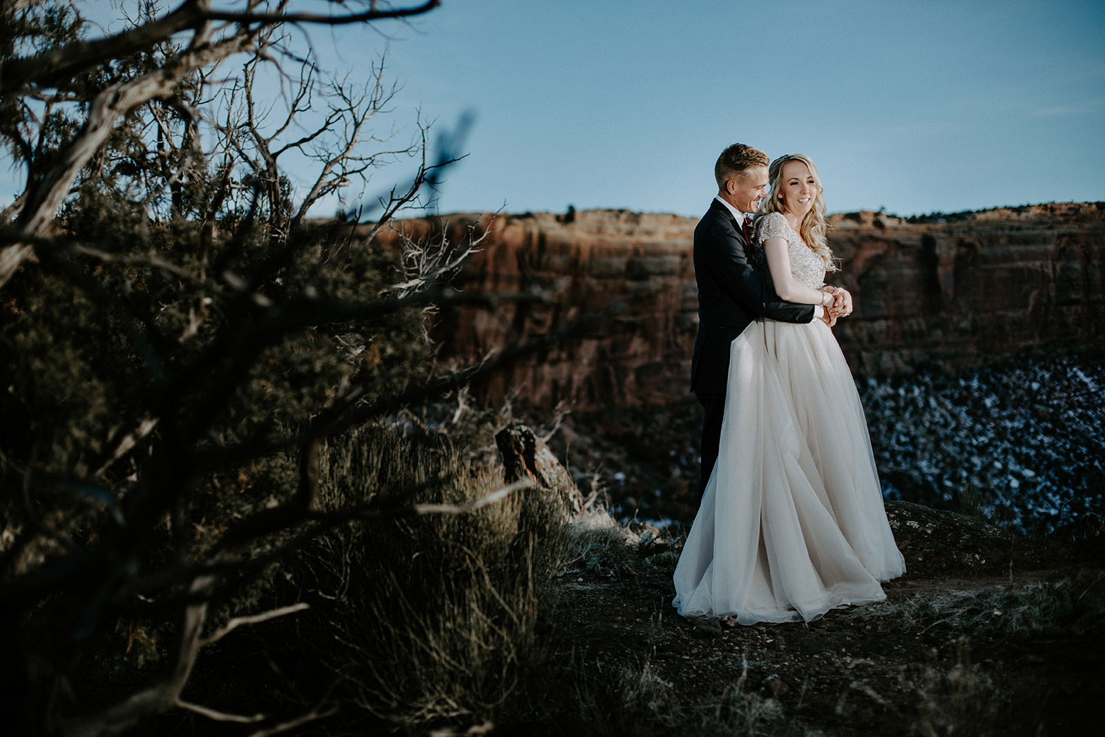 Bride and groom illuminated by off camera flash with cliffs behind them
