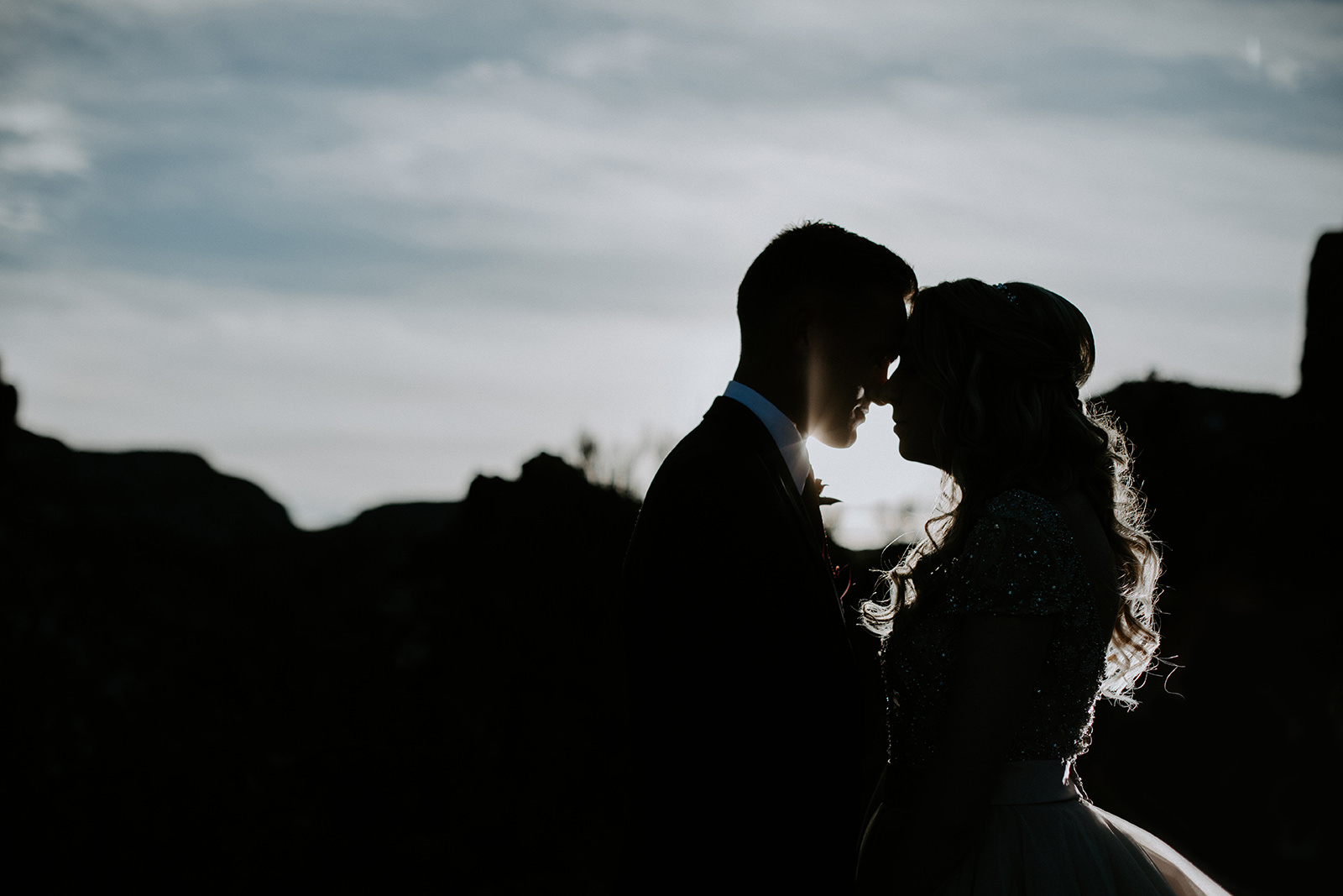 Silhoutte of groom and bride against cliffs in background with sun behind them