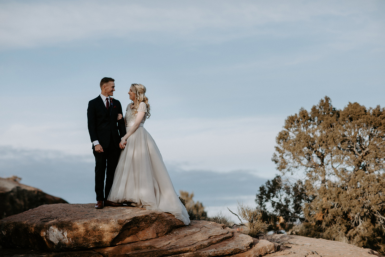 Just married couple standing on red sandstone with blue skies behind them