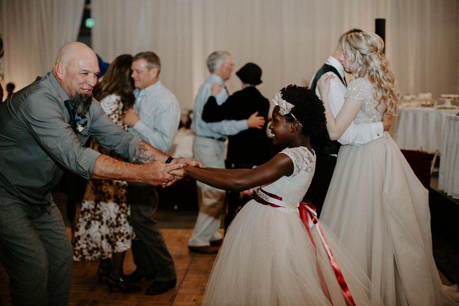Granddad dancing with granddaughter during dancing in ballroom