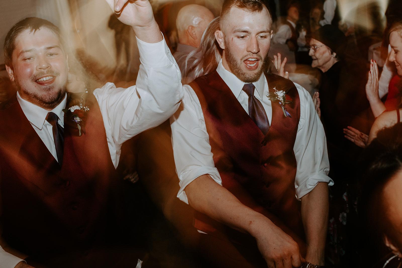 Groomsmen in red vests dancing during wedding reception