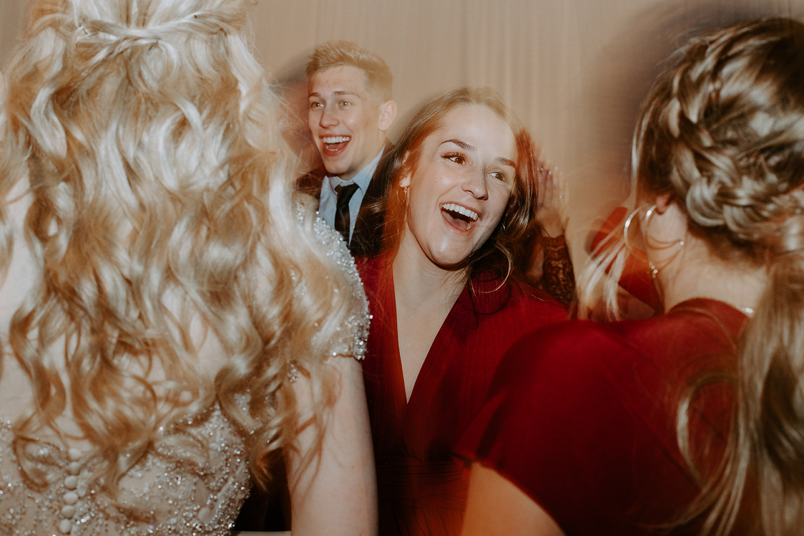 Bridesmaid in red dreas laughing between two friends