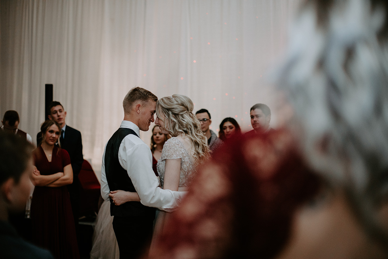 Older woman blurred in foreground looking at bride and groom in focus while dancing