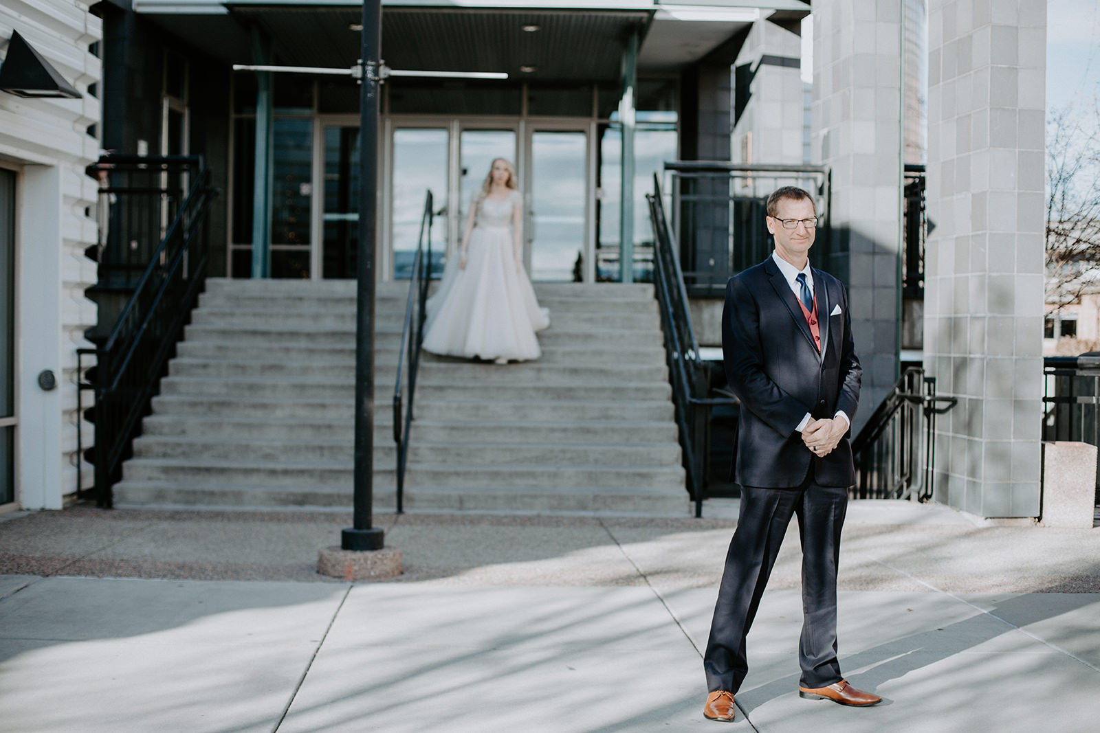 Dad stands in foreground waiting to see his soon to be married daughter walking down steps behind