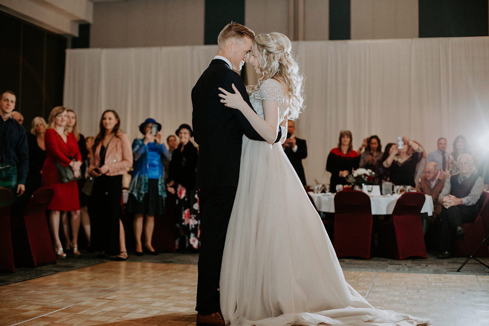 Bride and groom holding each other close during first dance with guest behind them