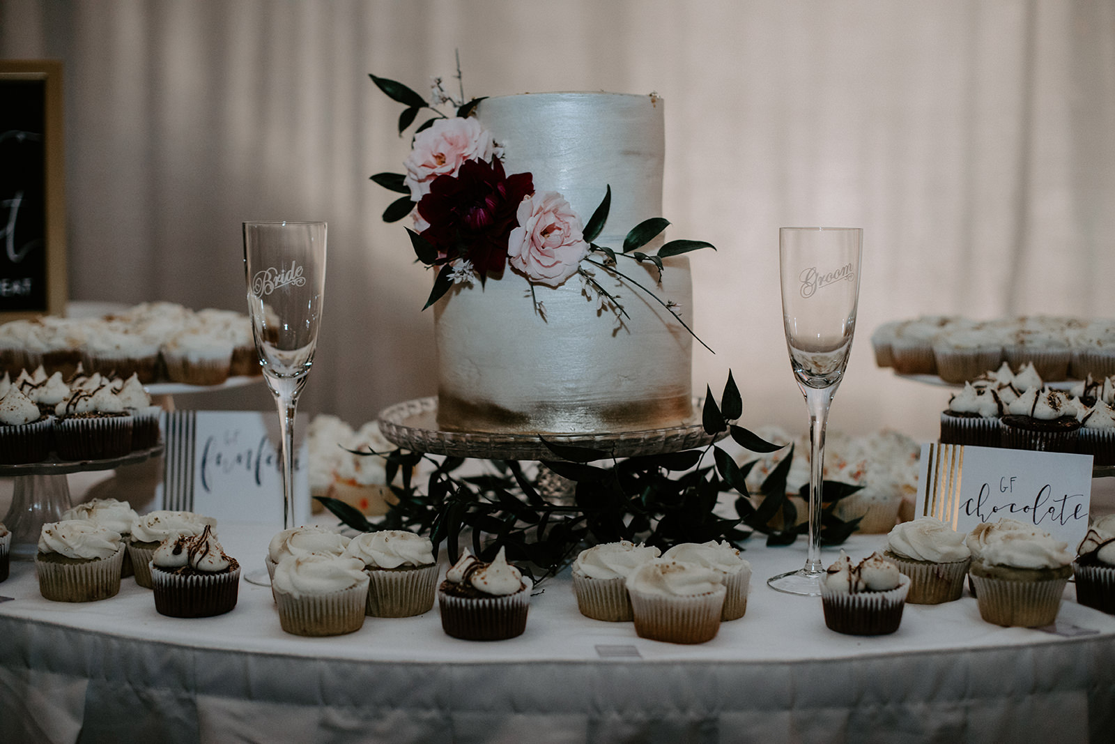 Close up of weddingcake and cupcakes with two wine glasses