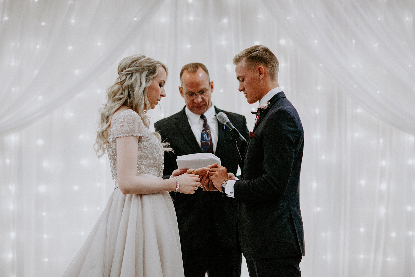 Groom slips on bride's ring during ceremony with white drapes and lights in background