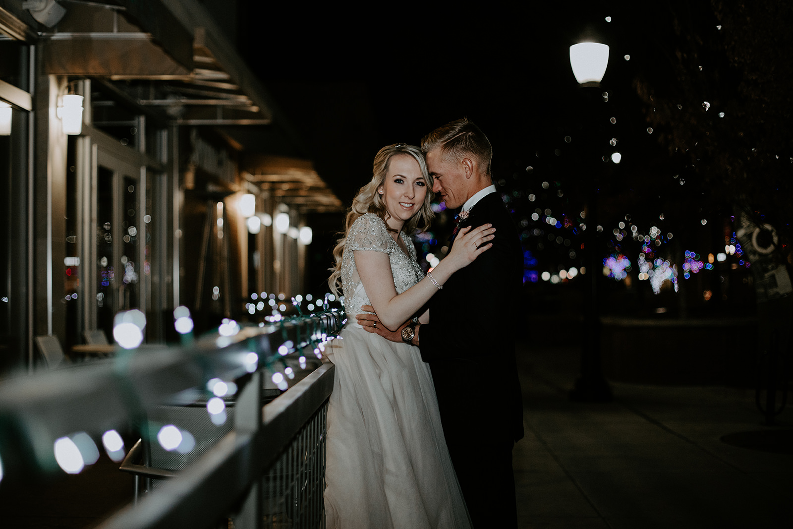 Bride facing camera with groom facing her at night with Christmas lights in foreground