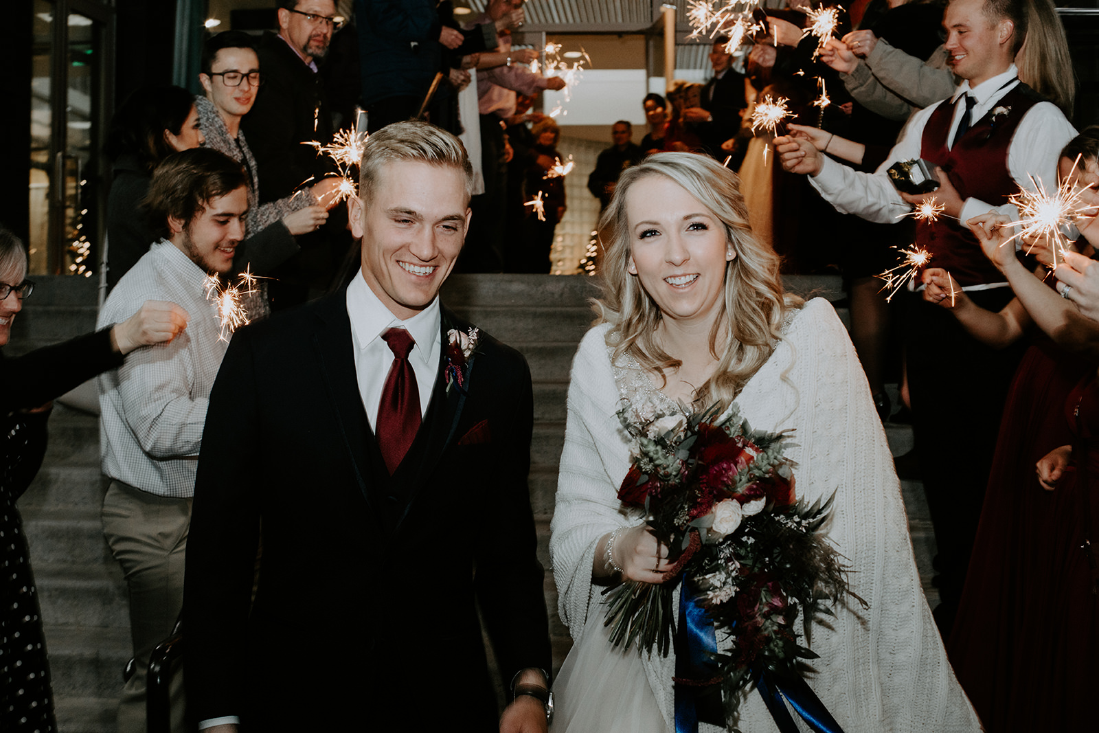 Smiling bride and groom walking down steps while guests hold sparklers during exit