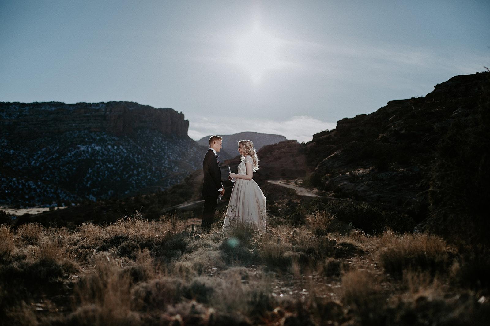 Wide view of bride in white dress and groom in dark blue suit in desert