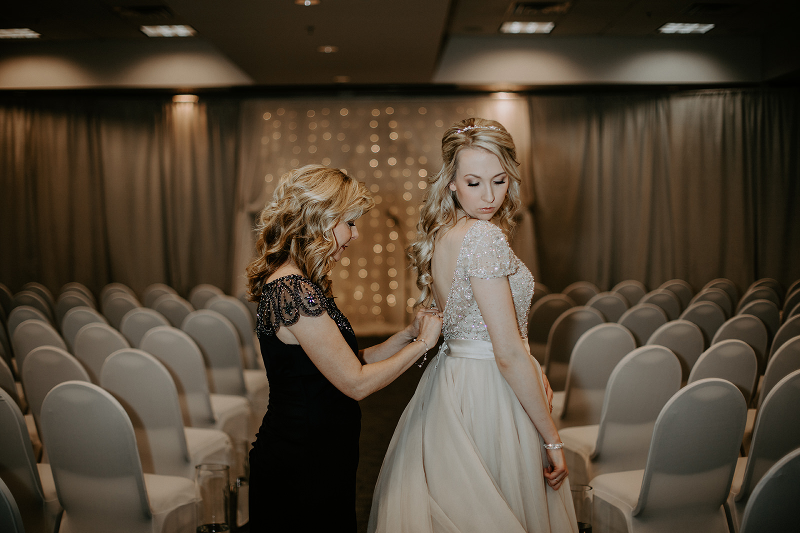 Mom buttoning bride's dress from behind in front of indoor ceremony site