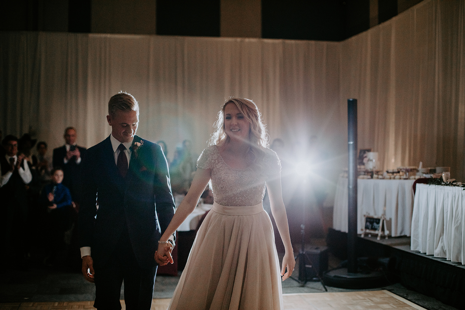 Couple holding hands after completing their first dance as a married couple