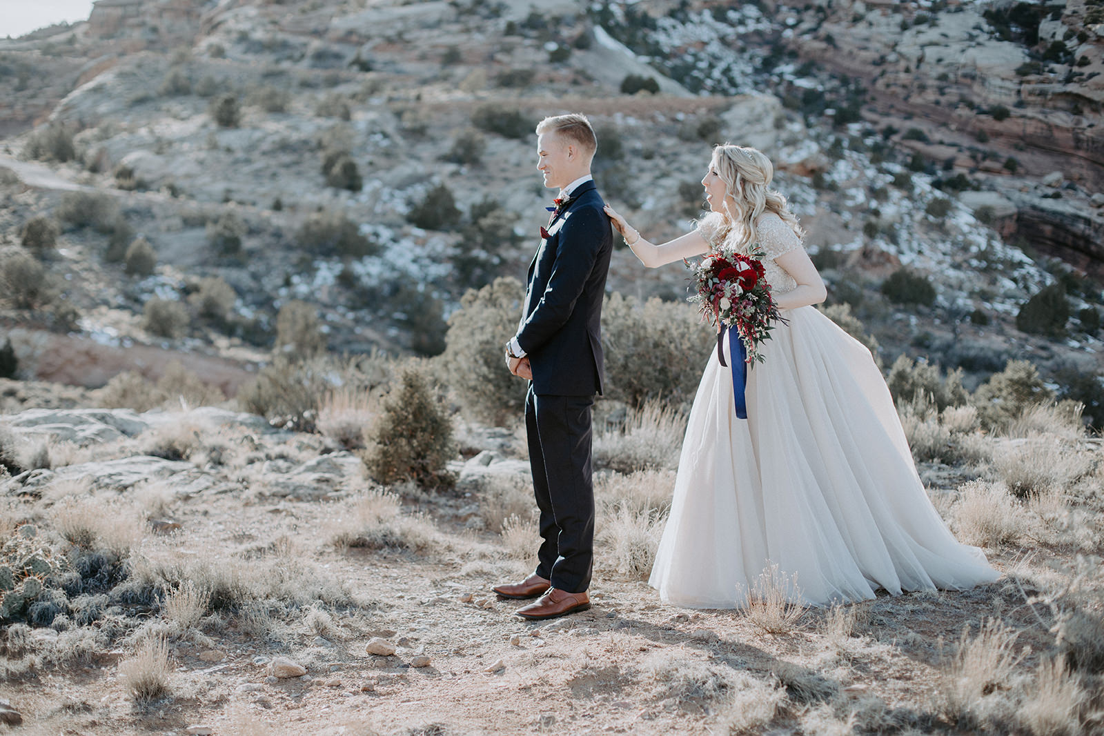 Bride tapping groom on shoulder during first look in desert of Grand Junction