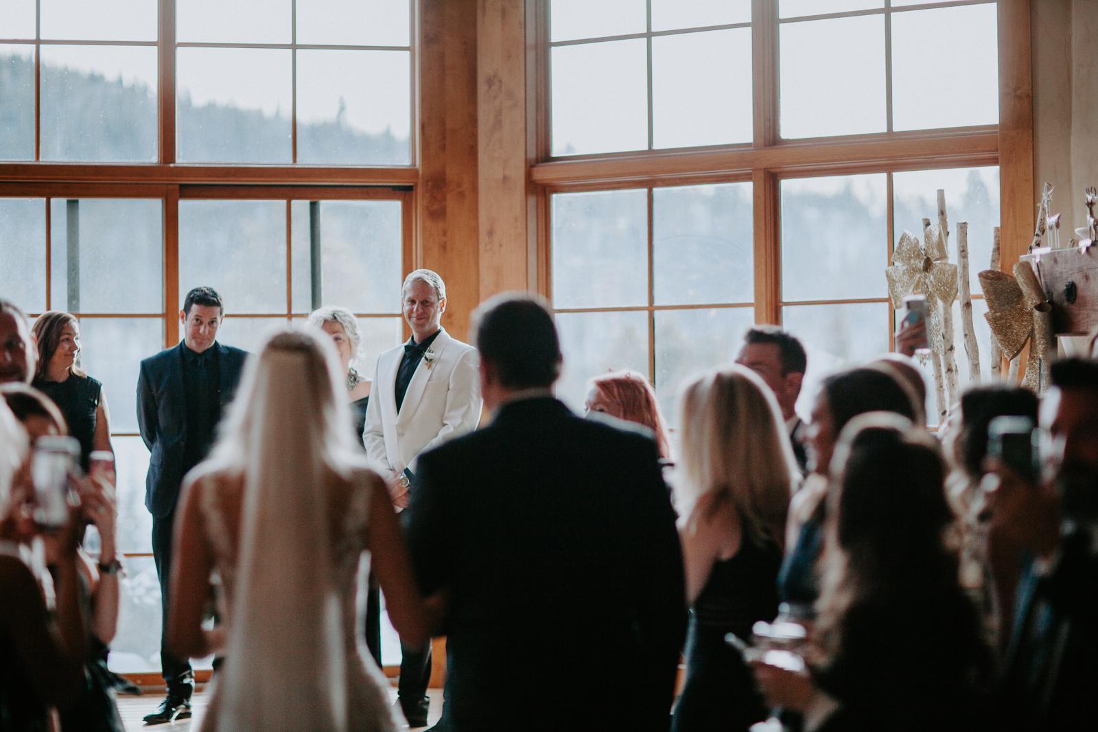 Groom in focus watching bride blurres walking down aisle