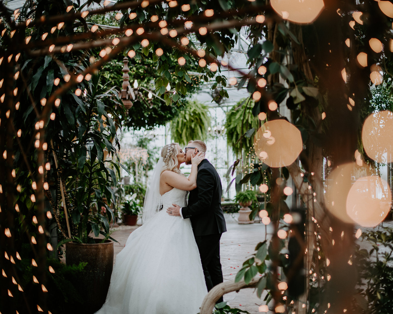 Bride and groom kissing among lights in greenhouse