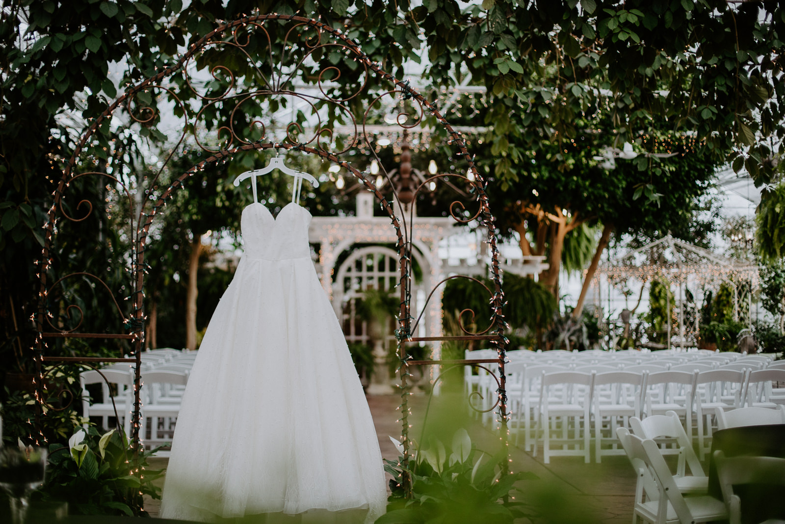 Wedding dress hanging in elegant location among greenery and vegetation