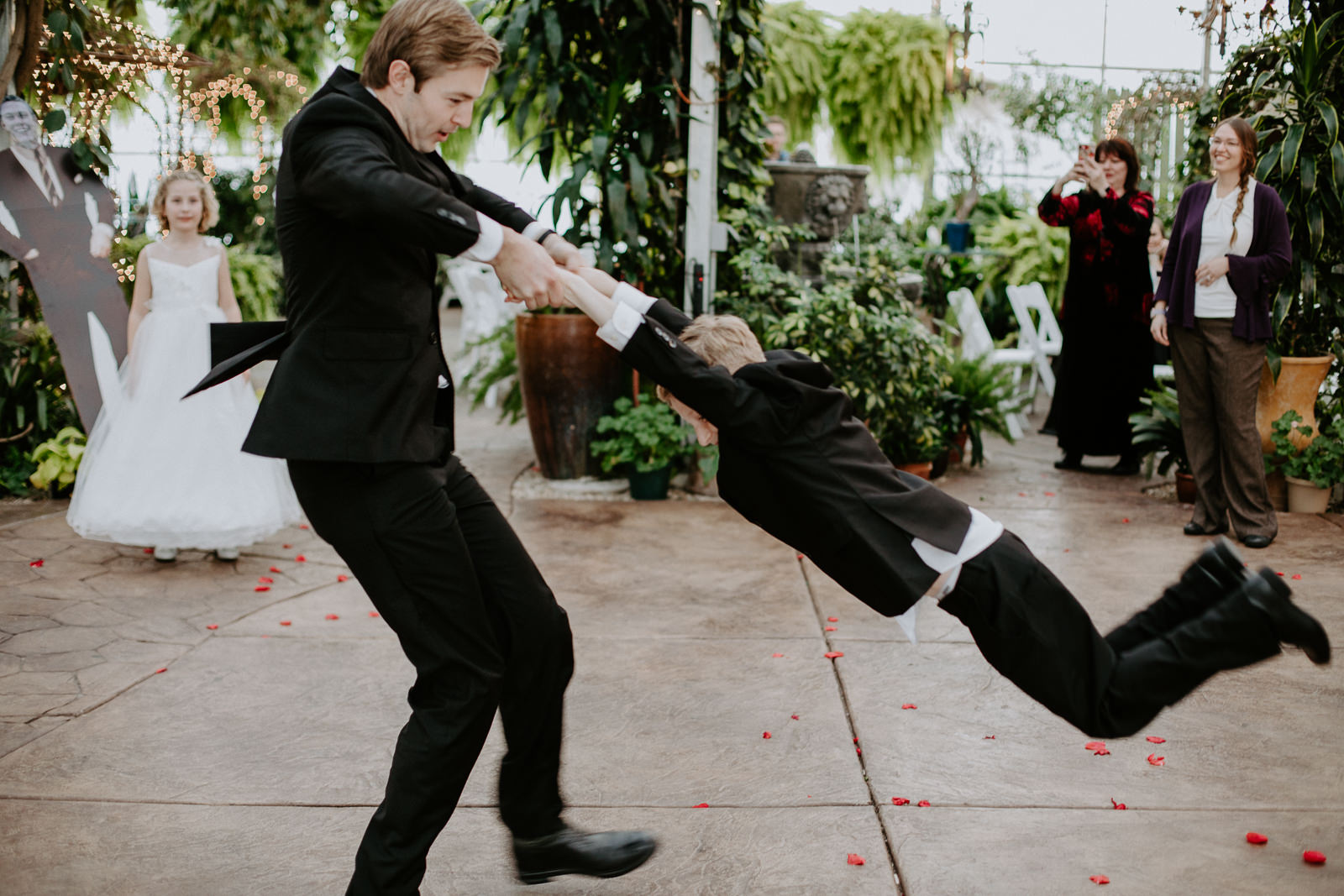 Best man swinging nephew around during dance after wedding