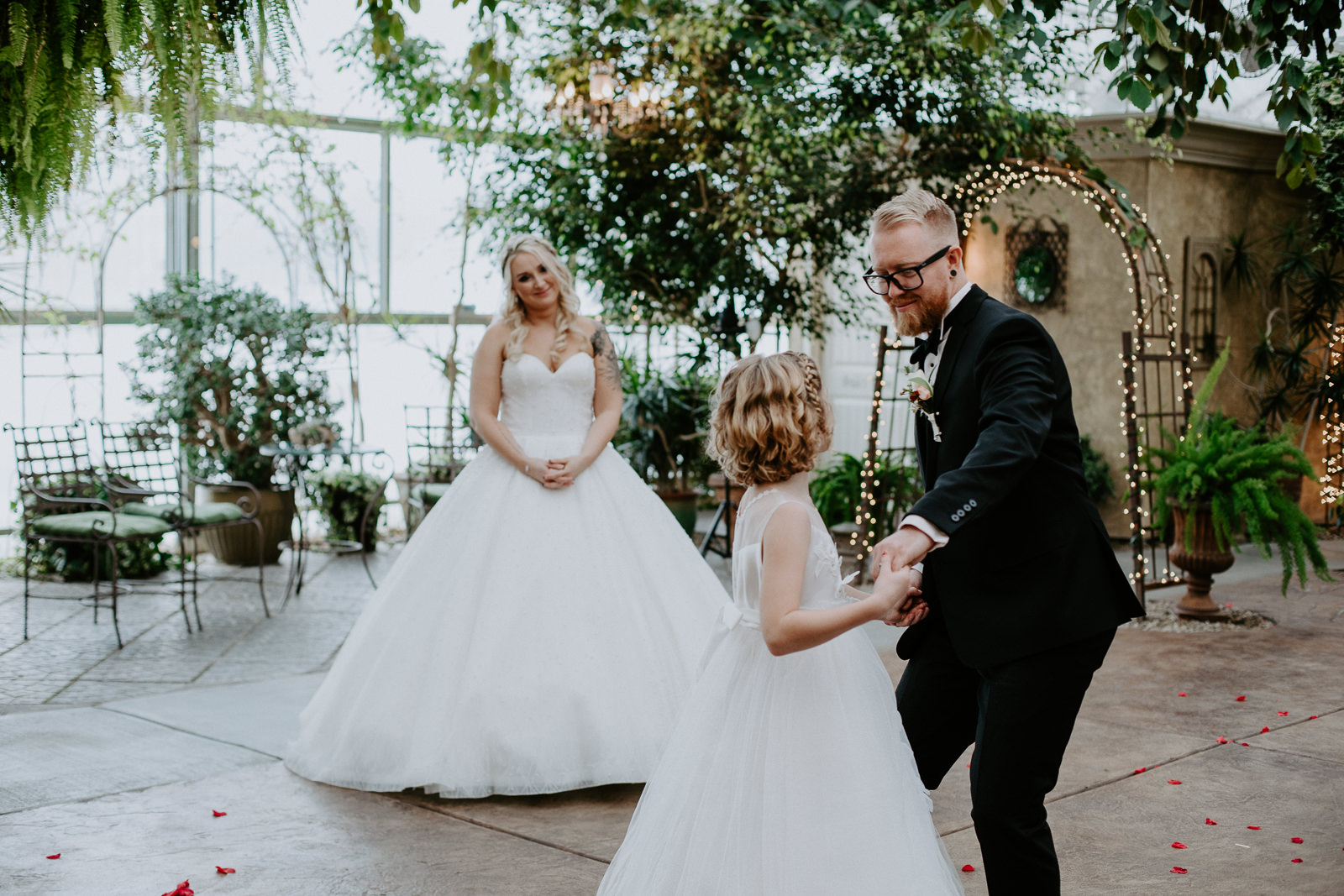 Bride looking on as her new husband dances with her daughter in candid moment