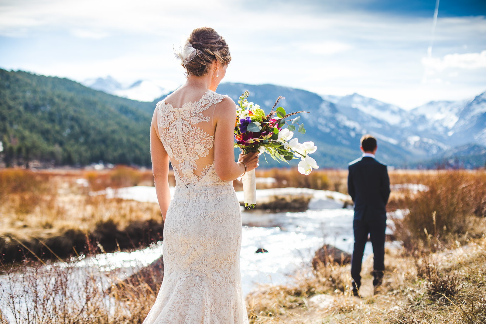 Bride approaching groom from behind for first-look in RMNP