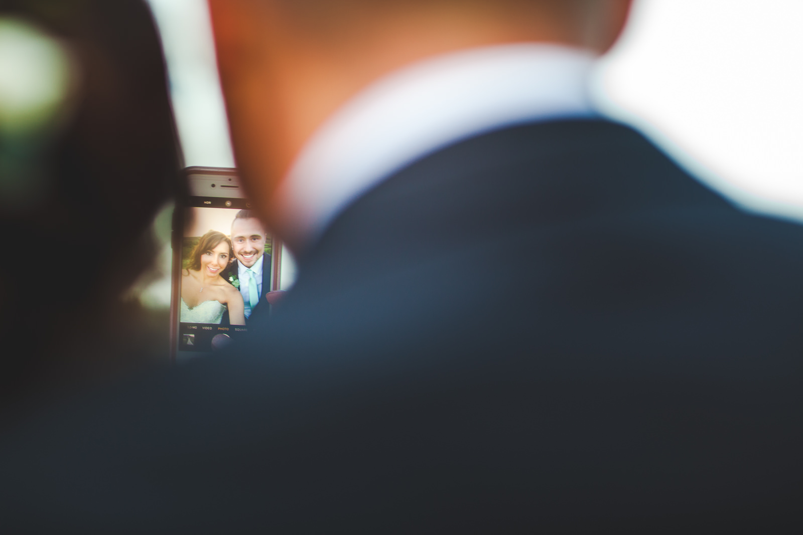 Catching an iphone selfie of a bride and groom couple from behind