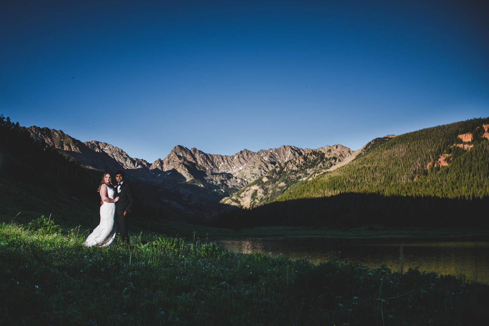 Bride in white dress and groom in tux standing in mountain meadow