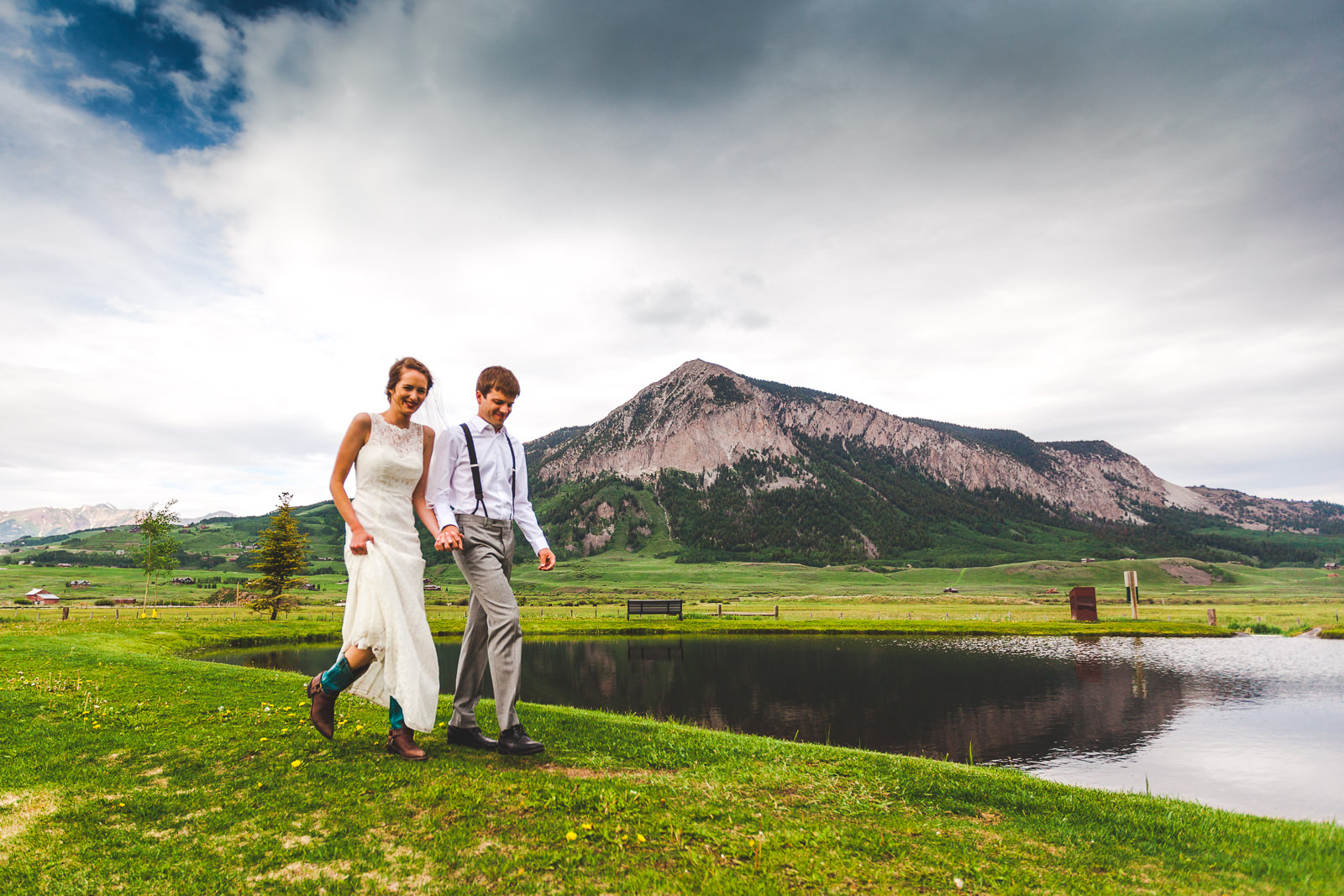 Just married couple walking along lake in front of Crested Butte Mountain