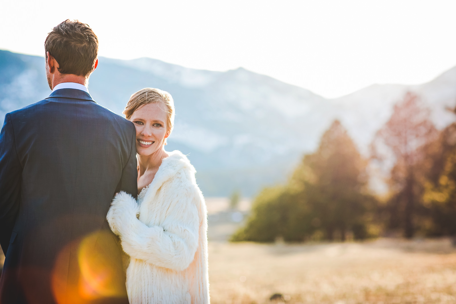 Bride holding arm of groom facing away with RMNP mountains in background