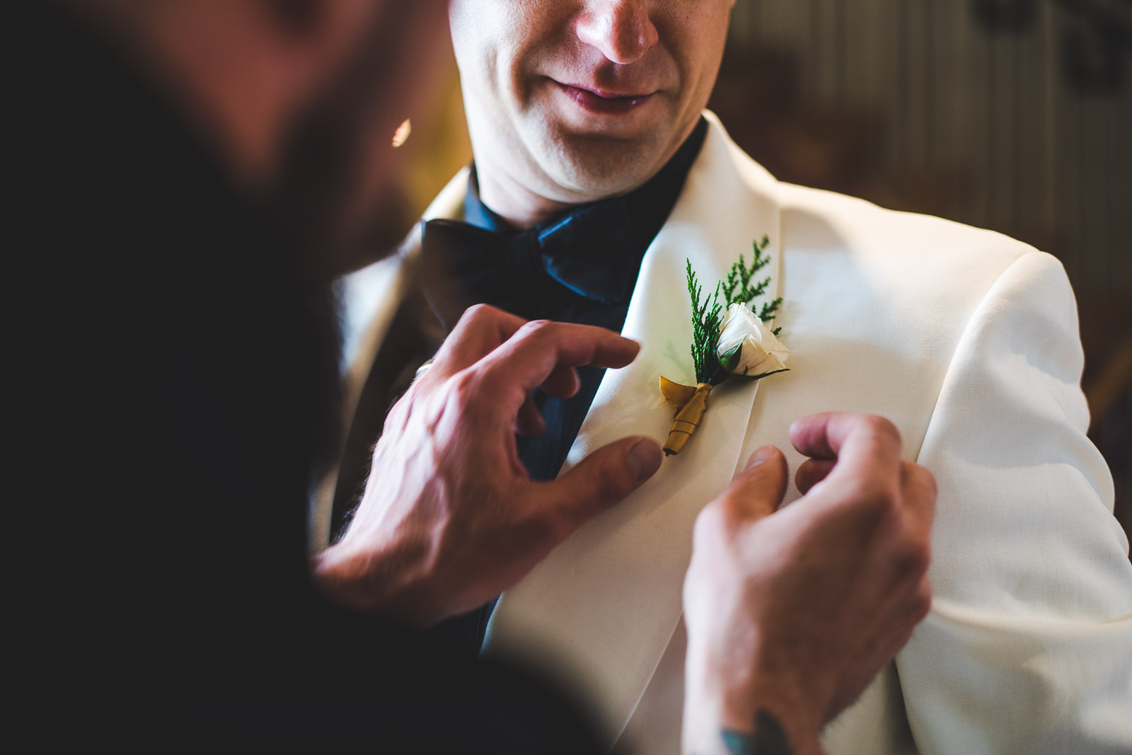 Detail of best man pinning boutonniere on groom's white suit jacket