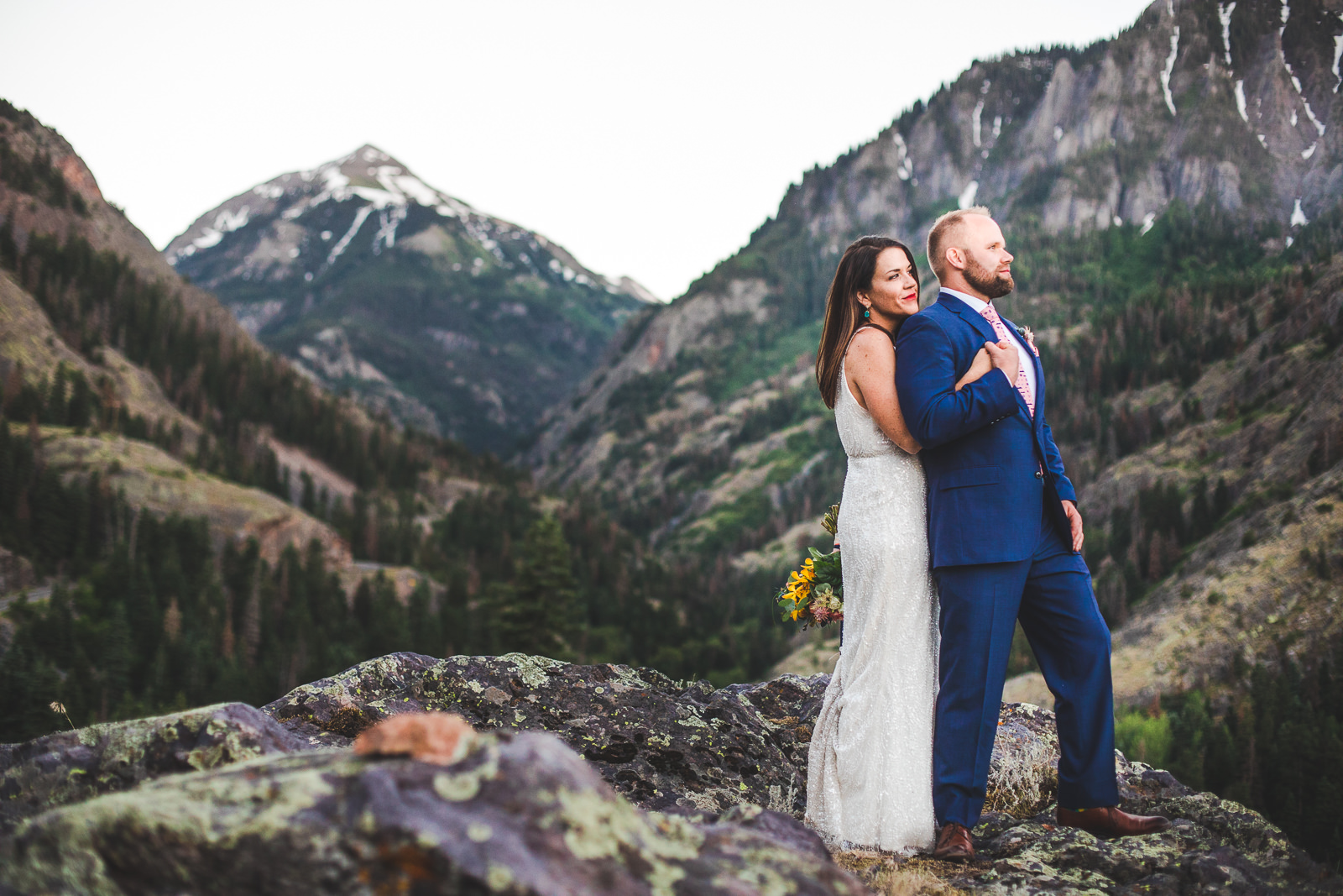 Bride holding groom from behind with San Juan mountains behind them