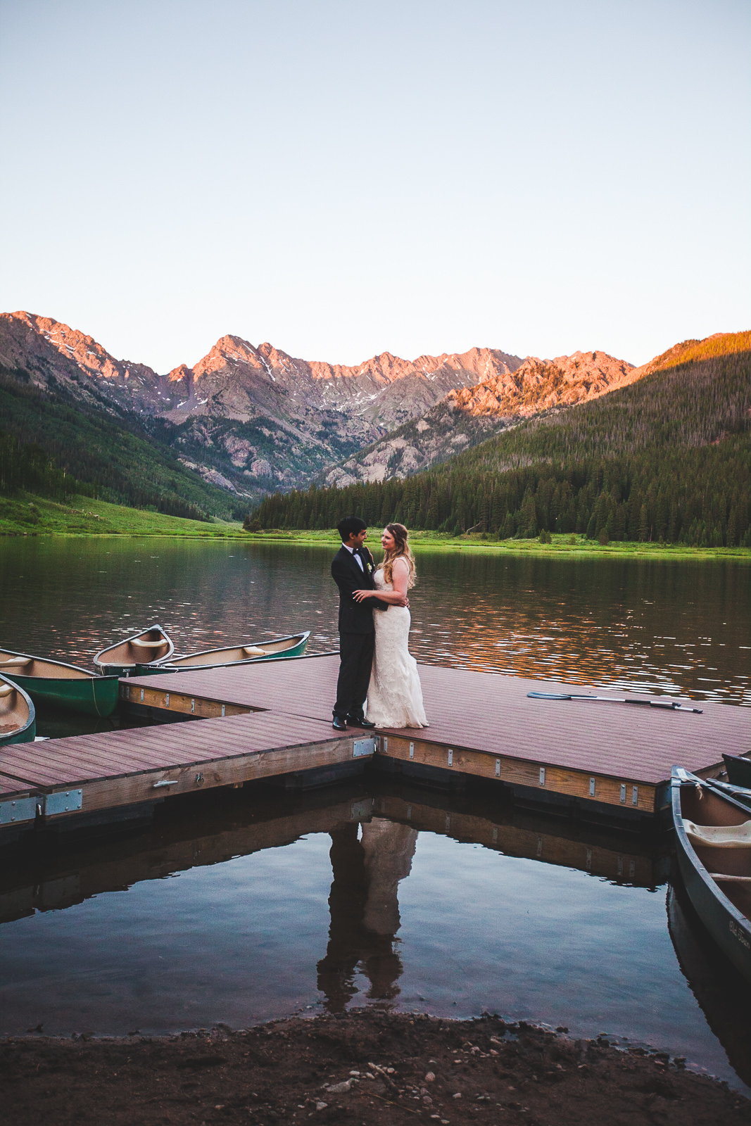 Wed couple standing on dock with mountains north of Vail