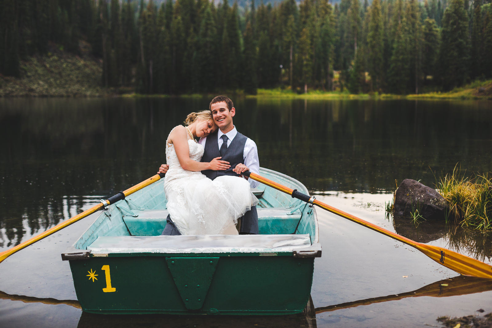 Bride and groom sitting and cuddling in boat at Mesa Lakes Lodge lake on  the Grand Mesa