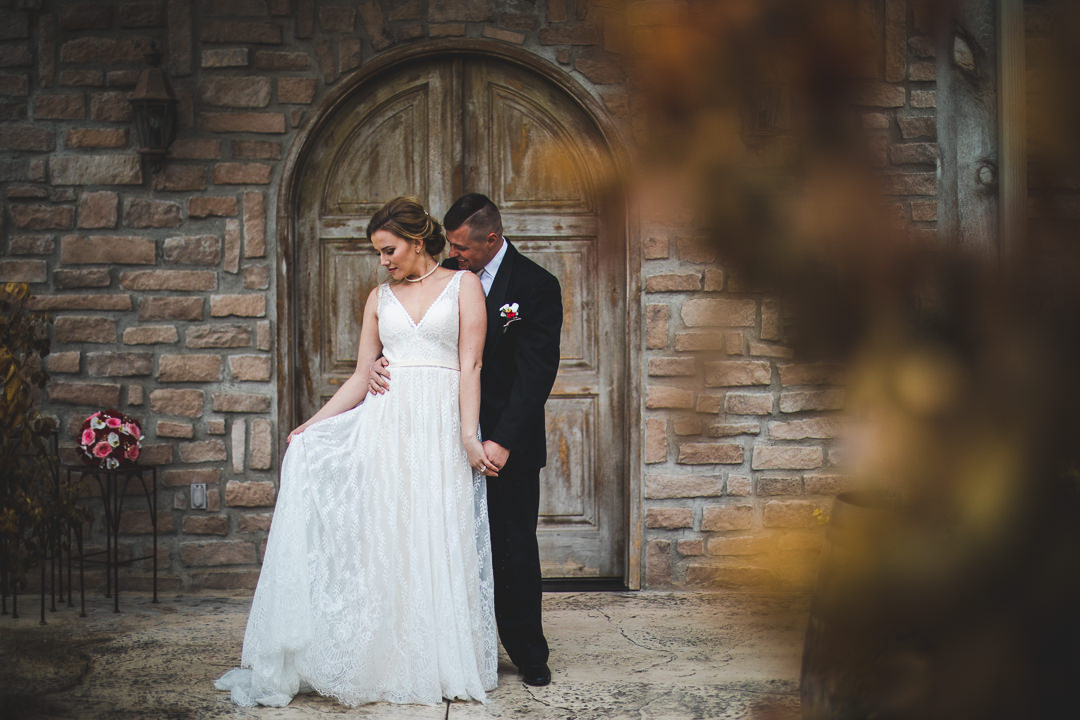 Bride holding dress with groom kissing her shoulder in front of arched winery door