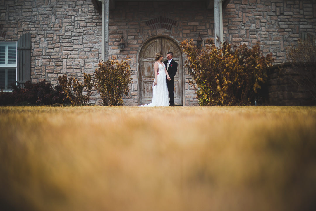 Grass in foreground of bride and groom in front of italian style winery