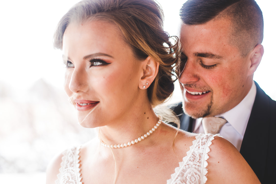 Closeup of bride and groom smiling with bright light behind