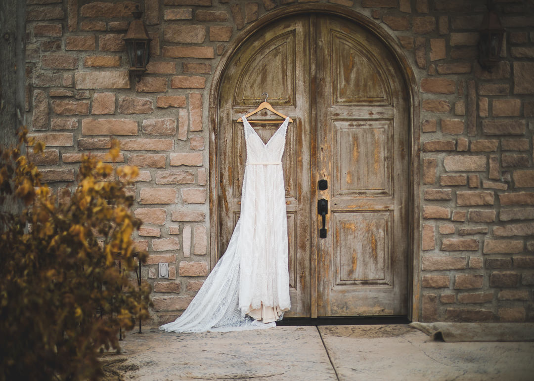 White wedding dress hanging on arched door