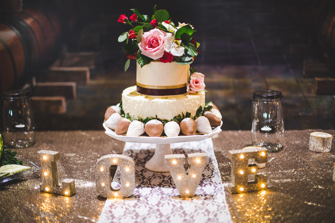 Wedding cake adorned with chocolate strawberries, green leaves, and flowers