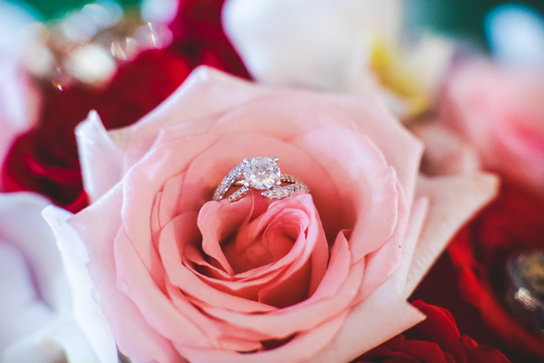 Wedding ring resting on pink rose