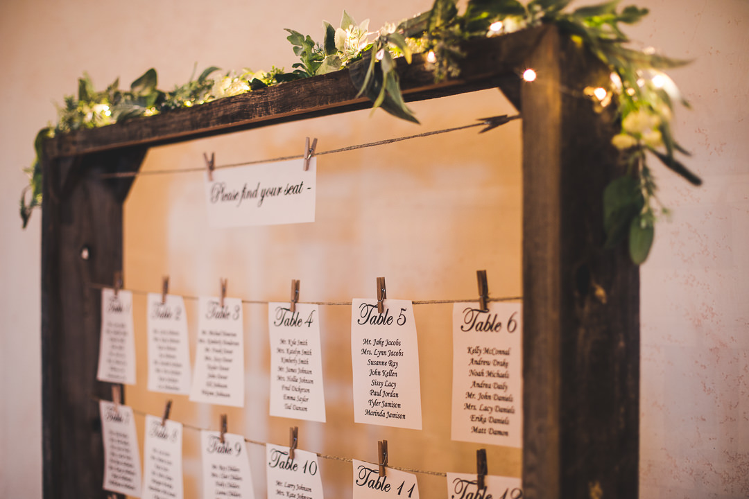 Table placards hang from rustic square hanger