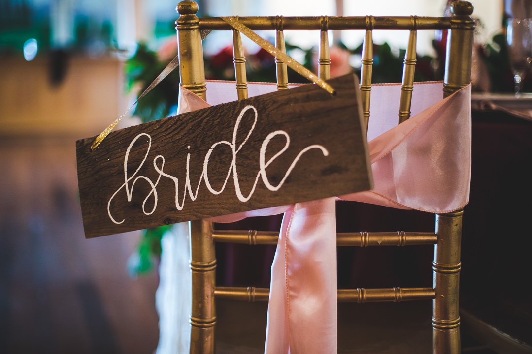 Rustic bride sign hanging on the back of chair