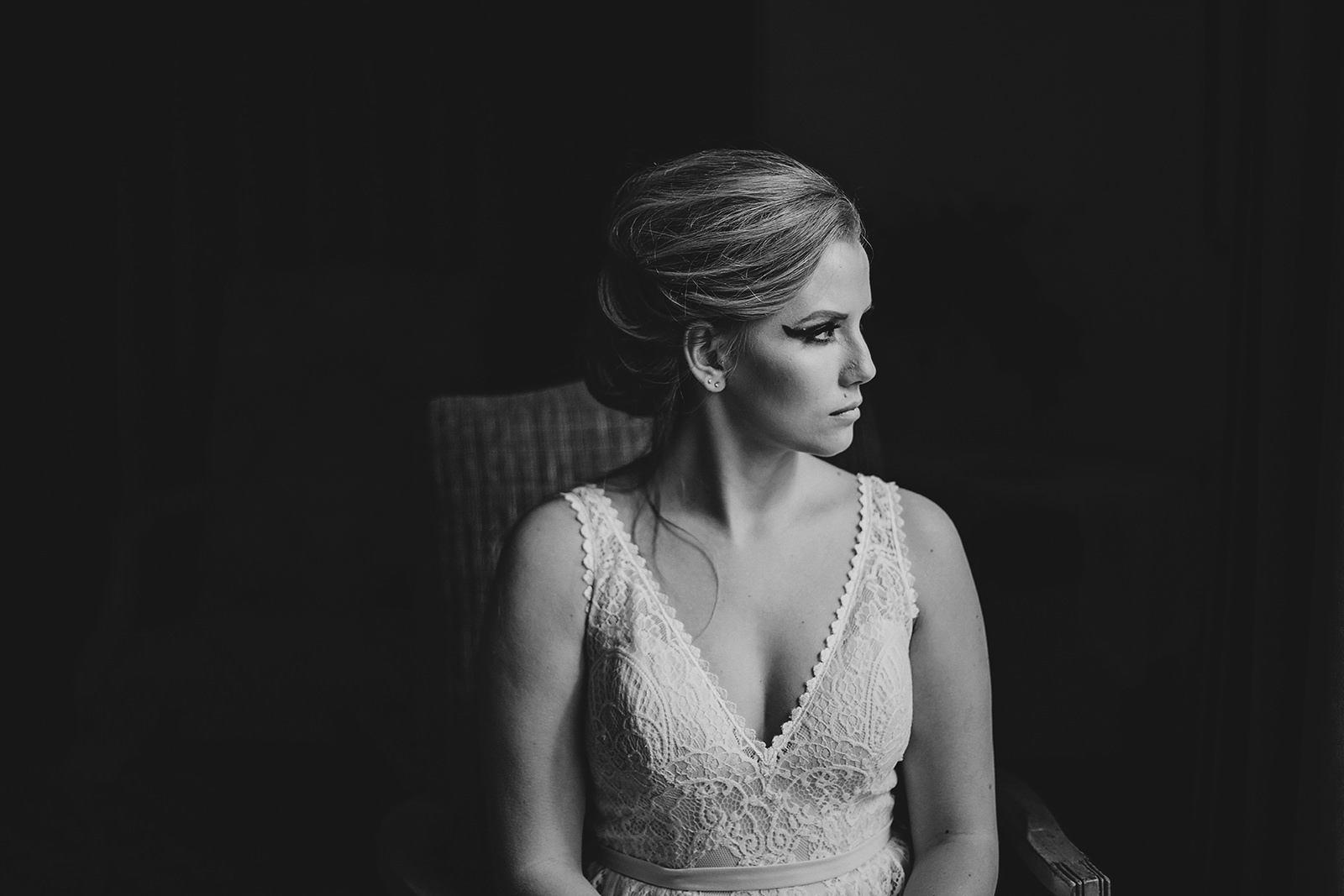 Bride looking out window with darkness around her