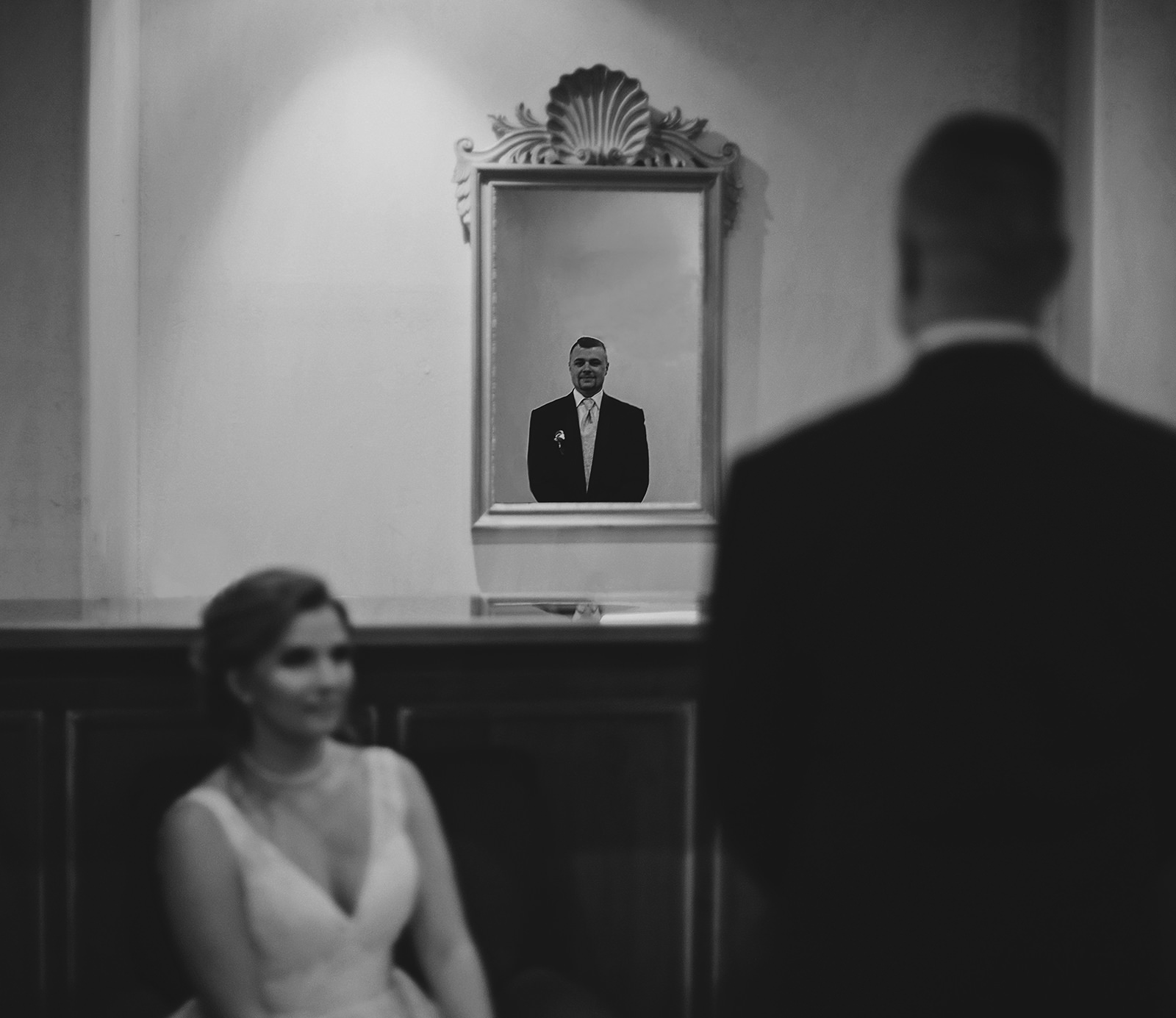 Bride looking at groom who is smiling and looking in mirror