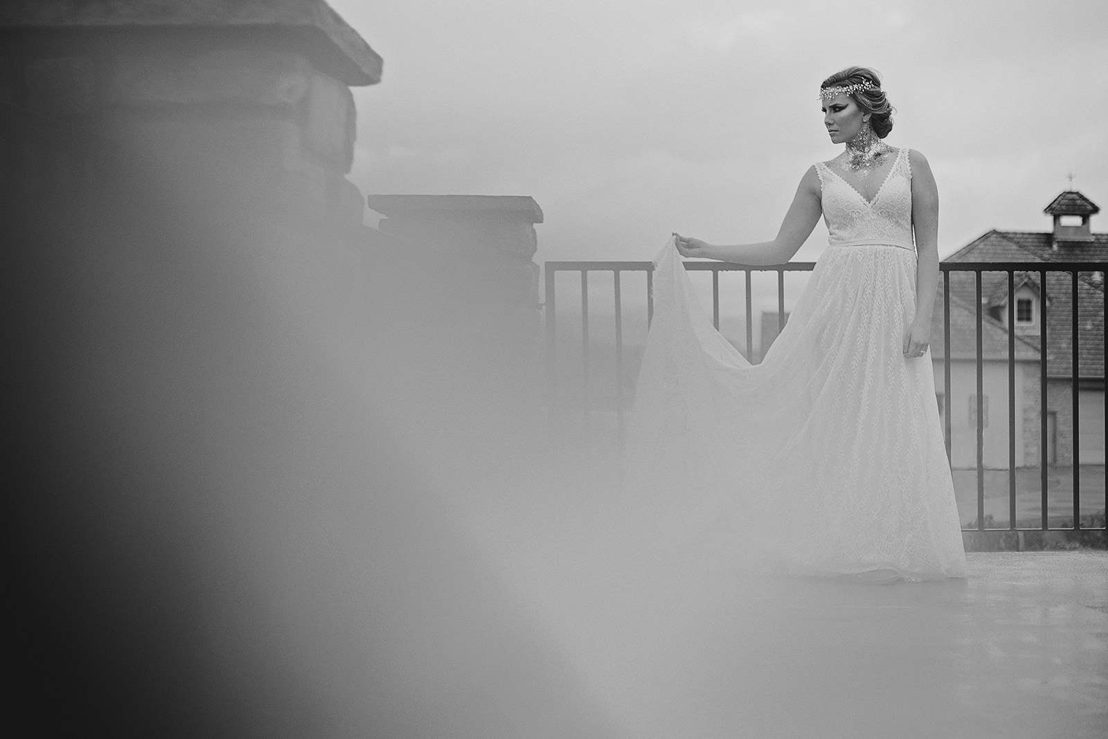 Black and white of bride holding dress on patio