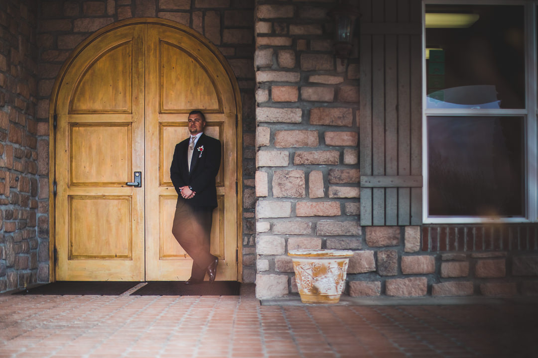 Groom leaning on door entry to winery