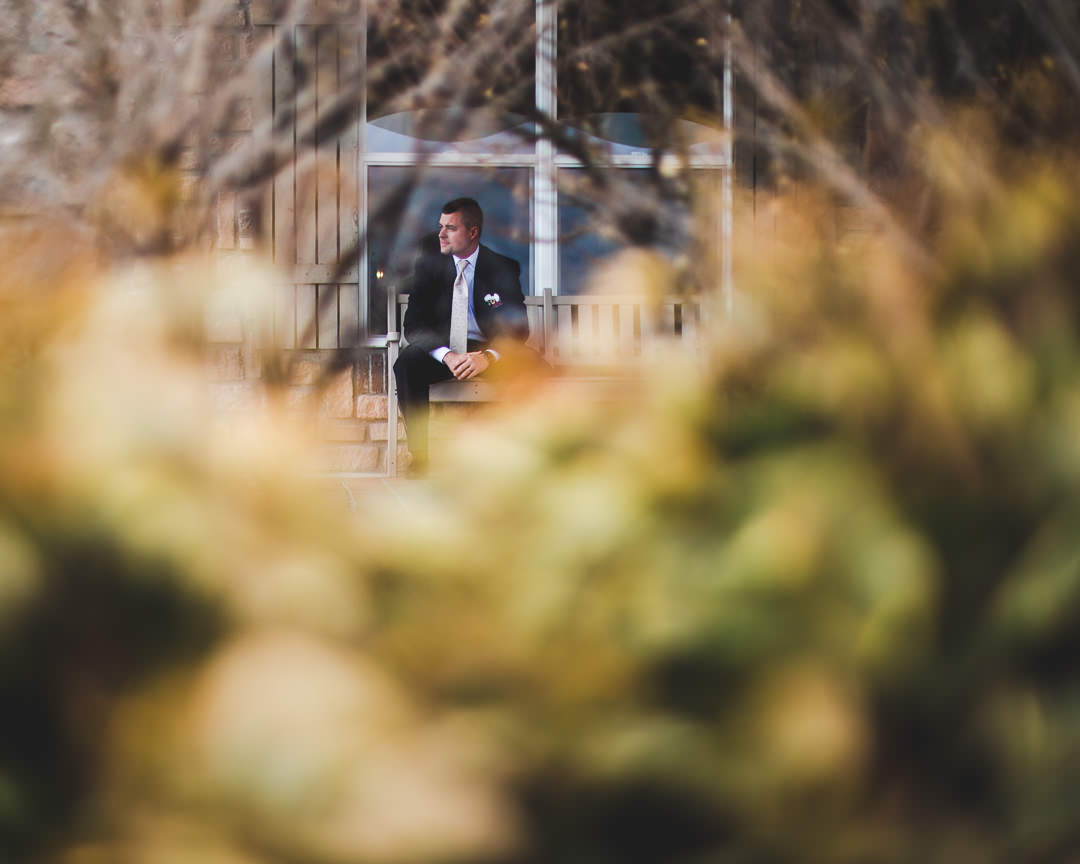 Groom seated on bench only visible through vegetation