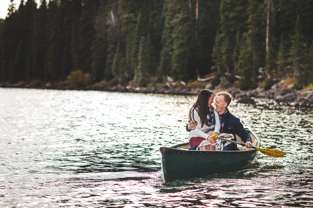 Couple smiling and embracing while on a canoe in a lake on the Grand Mesa