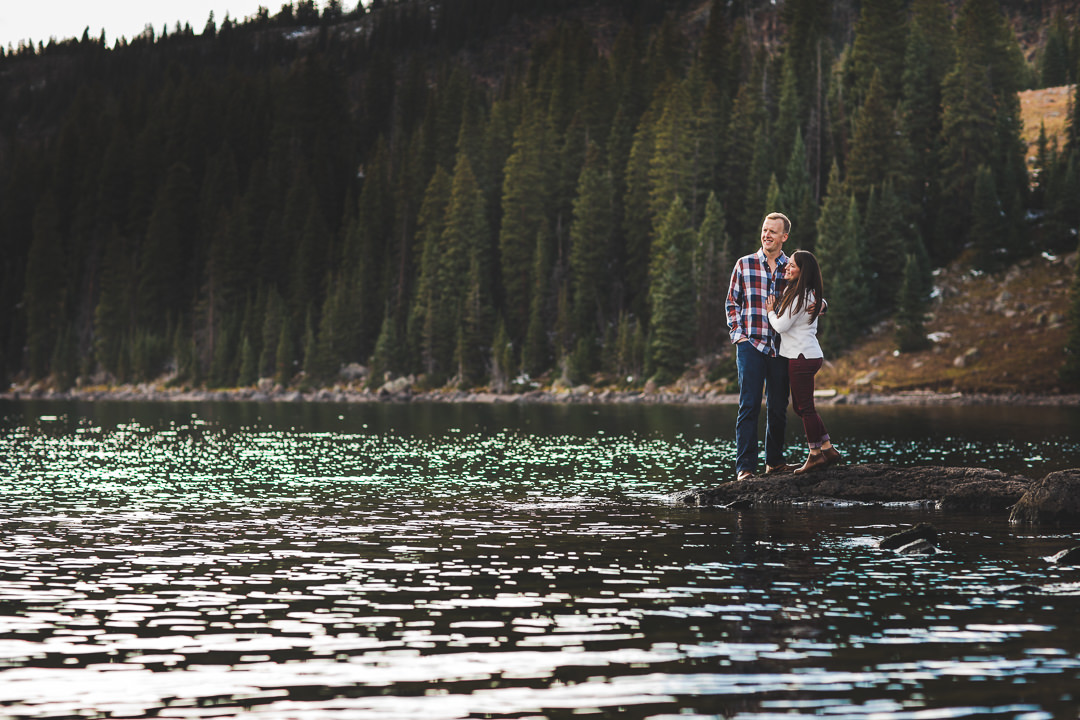 Engaged couple wearing coordinated fall attire while standing on the shoreline of a lake on the Grand Mesa