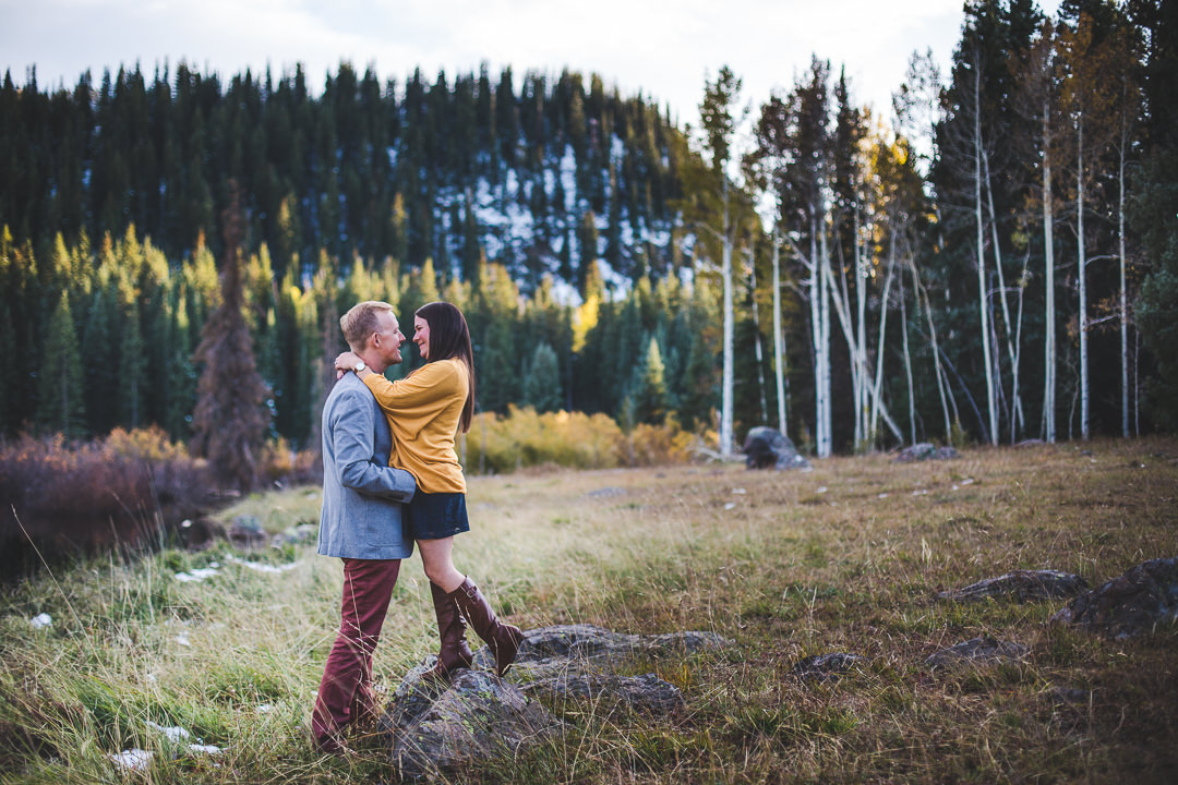 A great example of coordinated engagement session attire with couple hugging in meadow