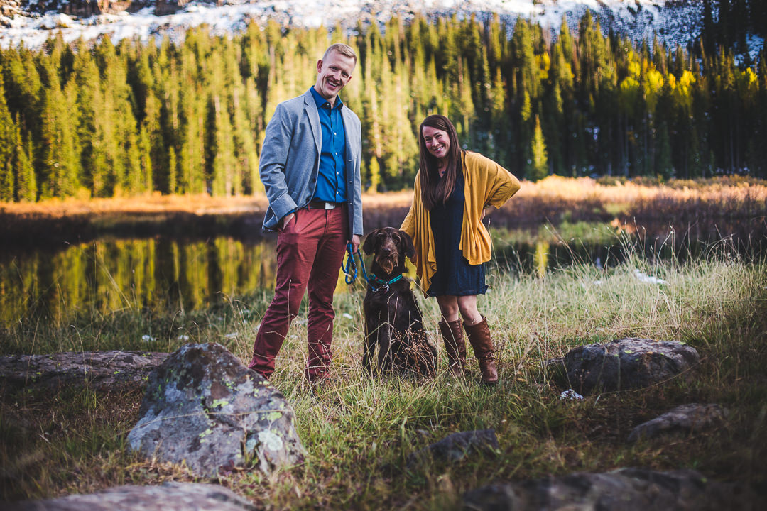 Couple in well coordinated engagement session attire standing with their dog in a fall meadow