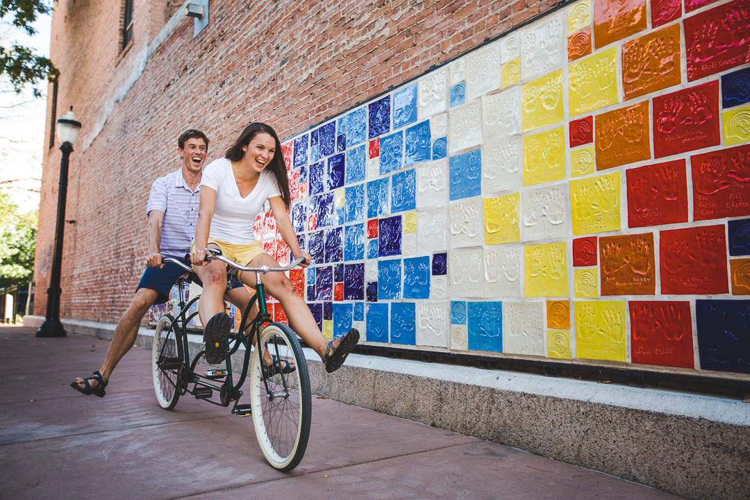 Goofy couple laughing while riding tandem bike no-footed down alley